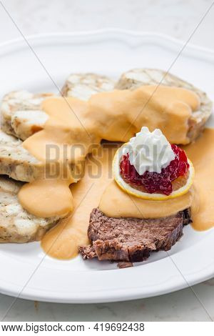 sirloin sauce with dumplings and cranberries on lemon with whipped cream
