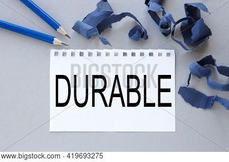 Durable. Text On White Notepad Paper. Near Torn Blue Paper