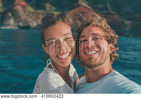 Cruise vacation happy tourists selfie smiling with perfect smile on outdoor nature adventure in ocean. Interracial couple Asian woman, Caucasian man.