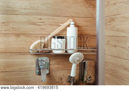 A Bath Sponge, A Body Massager Brush, A Penza, A Bottle Of Shampoo And Hair Balm Is On A Shelf In A