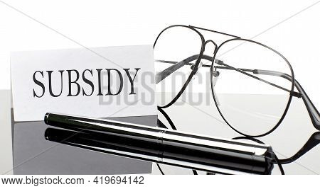 Text Subsidy On Paper On Light Background With Pen And Glasses. Business