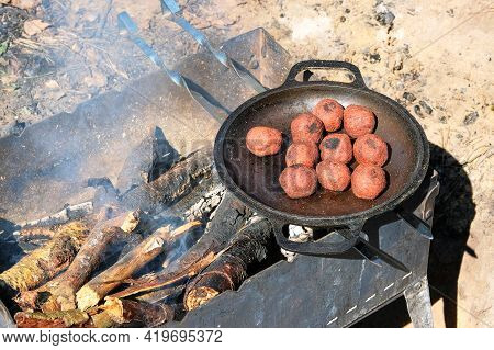 Falafel Cook In A Pan Outdoors. Middle East Culture. Wood Fire Prepared For Grill On Nature. Picnic.