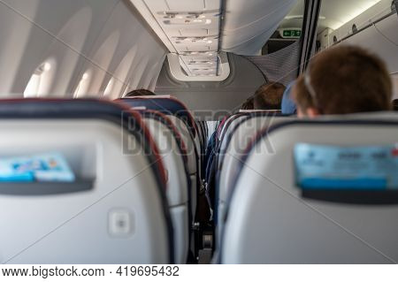 Interior Of Commercial Airplane With Unrecognizable Passengers On Their Seats During Flight Shot Fro