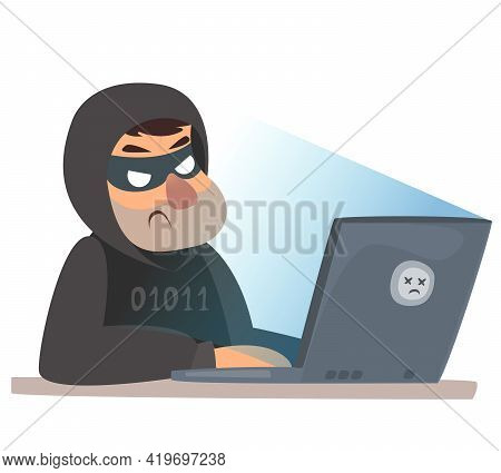 A Man At A Computer In A Criminal Mask. Computer Hacking Cyber Attack. The Villain Is Hacking The Si