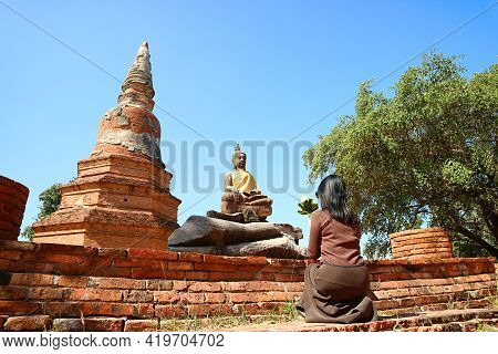 Woman Praying In Front Of Buddha Image At Wat Phra Ngam Temple Ruins In Ayutthaya, Historic Place In