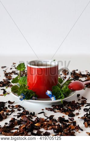 Red Teacup On A White Table With Leafs And Flowers With White Background And Tea Scattered