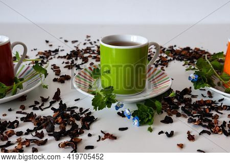 Green Teacup On A White Table With Leafs And Flowers With White Background And Tea Scattered
