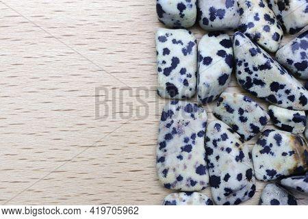 Dalmatian Jasper Heap Jewel Stones Texture On Half Light Varnished Wood Background. Place For Text.