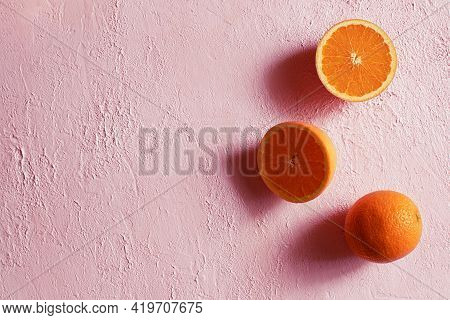 Whole And Cut In Half Ripe Orange On A Pink Concrete Surface. Minimalism. Copy Space