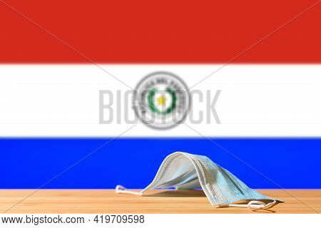 A Medical Mask Lies On The Table Against The Background Of The Flag Of Paraguay. The Concept Of A Ma