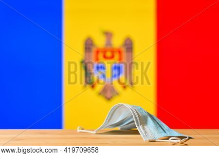 A Medical Mask Lies On The Table Against The Background Of The Flag Of Moldova. The Concept Of A Man