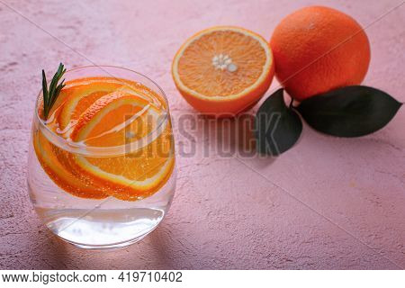 Refreshing Detox Lemonade With Sliced Orange And An Orange Cut In Half And Sprig Of Rosemary On A Pi