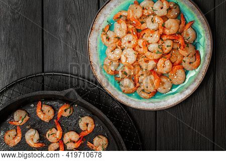 Prawns Fried With Garlic On A Blue Porcelain Plate And In A Black Cast Iron Skillet On A Black Woode