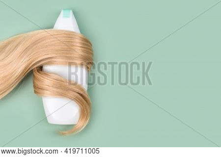 Shampoo Or Conditioner Bottle Wrapped In Lock Of Curly Blonde Hair On Light Mint Background, Top Vie