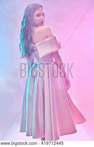 Attractive girl in an elegant evening dress poses at the studio in gentle pink light. Evening fashion.