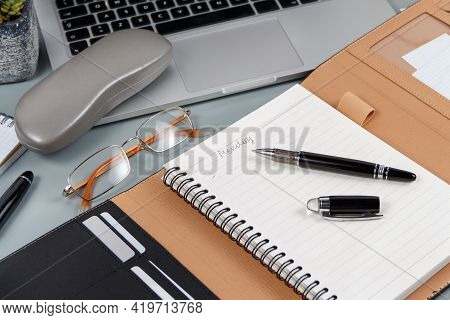 Opened Agenda With Handwritten Monday Near Glasses And Laptop On A Grey Table Close Up