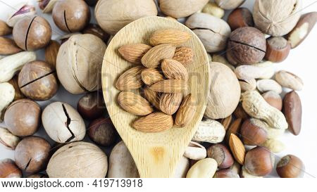 Nuts Almonds Close-up In A Wooden Spoon On The Background Of A Scattering Of Different Nuts. Assorte