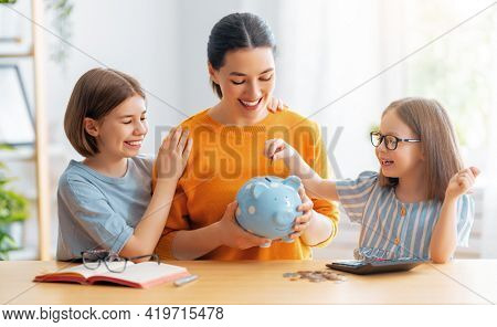 Woman and children sitting at desk with a piggy bank are calculating expenses, managing the family budget.