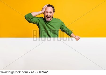 Photo Of Amazed Man Hold White Banner Palm Head Empty Space Wear Green Pullover Isolated Yellow Colo