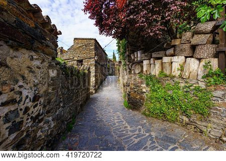 Narrow Alley Of Old Town With Old Houses And Stacked Firewood Logs. Patones De Arriba Madrid. Spain.