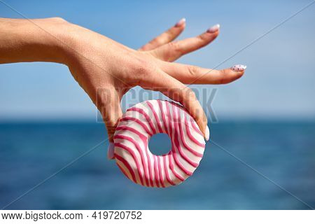 Shallow Depth Of Field Doughnut In Hand On Blue Sky And Sea Background. Concept Of Sweet Snack On Va