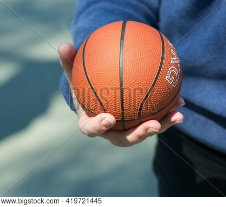 The Human Hand Holds The Ball. The Ball Is Orange. The Man Just Caught A Mini-basketball Ball.
