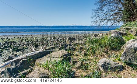 Rocks Cover The Shore At Low Tide In Des Moines, Washington. Olympic Mountains In The Distance.