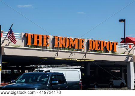 NORWALK, CONNECTICUT - MAY 6, 2021: Large  Home Depot sign with blue sky a cars