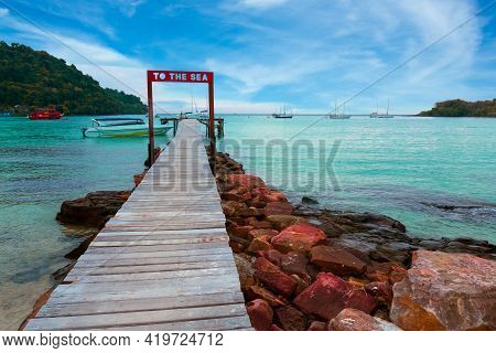 Wooden Bridge At Koh Kood Island With Emerald Green Water In The Clear Blue Sky During The Daytime.