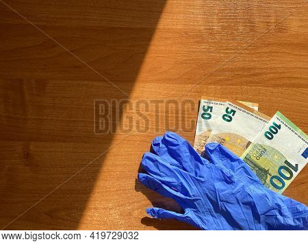 Blue Latex Gloves And 50 And 100 Euro Bills. In The Corner. Copy Space. For The Cashier Or Seller. S