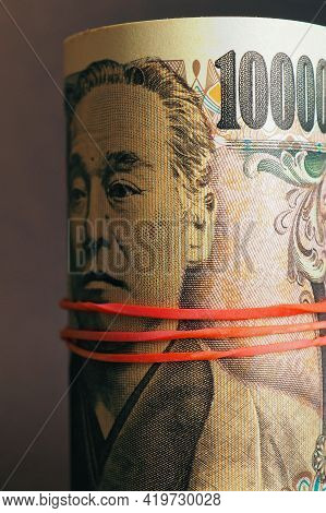 Japanese Money: Ten Thousand Yen Bills Are Rolled Up And Tied With An Elastic Band. Focus On The Num