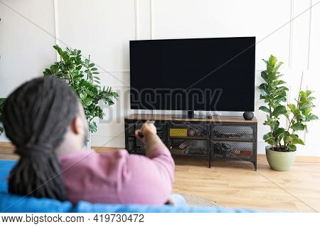 Back View African-american Guy With Dreadlocks Holds Remote Controller And Switching Tv Channels, Wa