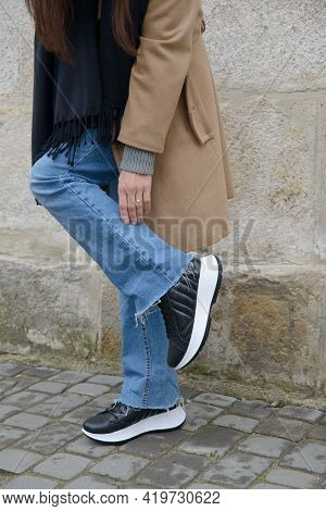 Stylish Young Girl Posing. She Is Wearing A Beige Coat, Jeans And Stylish Leather Sports Shoes