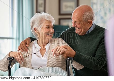 Romantic senior husband embracing disabled wife sitting on wheelchair at nursing home. Cheerful old couple embracing and looking at each other with love. Elderly man holding hands of handicapped woman