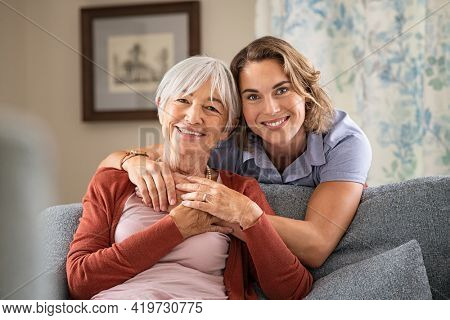 Cheerful mature woman embracing senior mother at home and looking at camera. Portrait of elderly mother and middle aged daughter smiling together. Happy loving daughter hugging from behind elderly mom