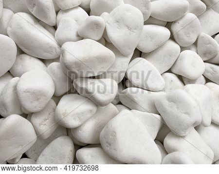 The Background Is Made Of White Smooth Pebbles Of White Color. Textured Background Of White Pebbles