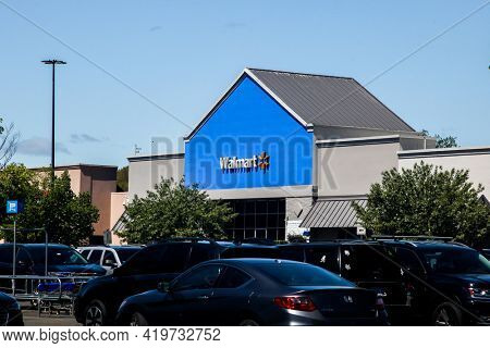 NORWALK, CONNECTICUT - MAY 6, 2021: Walmart storet sign with blue sky and  cars on parking lot
