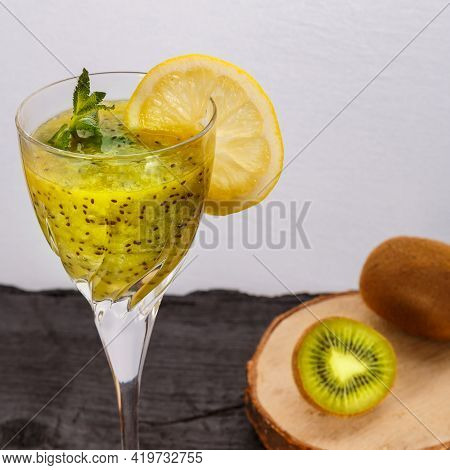 Kiwi Smoothie Garnished With Mint And Lemon In A Glass On A Gray Background Near Kiwi. Square Frame