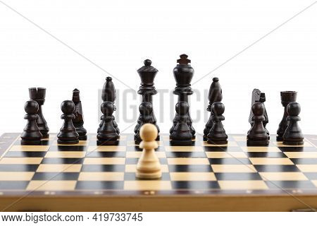 Wooden Chess. One Darling Pawn, Against All Black Pieces. Chess Pieces Are Located On A Chessboard.