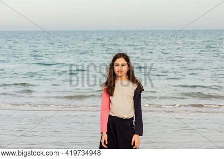 A Teenager Girl Stands By The Sea. Sea Vacation Concept. Girl, Teenage, Beach