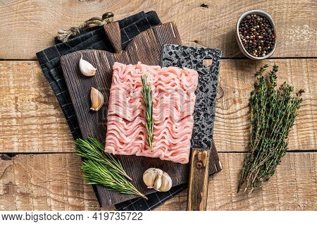 Raw Minced Chicken And Turkey Meat On Wooden Chopping Board With Butcher Cleaver. Wooden Background.