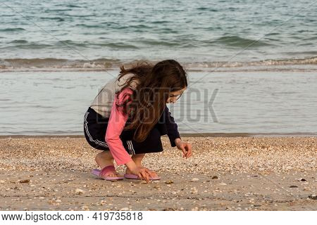 Sea Vacation Concept. Girl, Teenage, Beach. Teenager Girl Collects Seashells On The Beach By The Sea