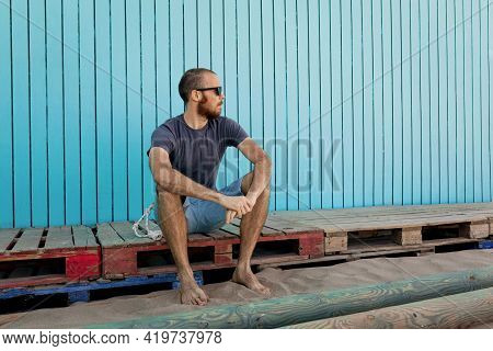 Bearded Young Man Wearing Sunglasses Is Confidently Looking Away At The Isla Canela Beach With A Blu