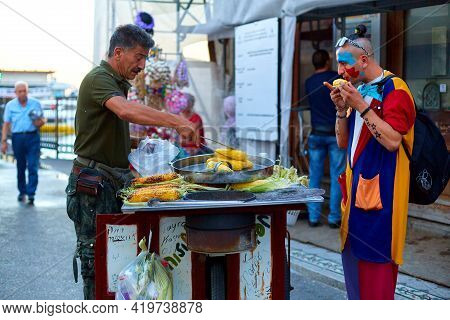 A Street Vendor Fries And Sells Corn On A City Street. The Guy Is Eating Corn On The Street. Istanbu
