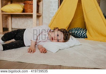 A Little Tired Girl Is Lying On The Floor With Her Head On A Pillow, Next To A Yellow Teepee. Rest A