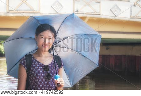A Chinese Woman Standing Near A Bridge And Water Canal Holding An Umbrella In The City Of Melaka Mal