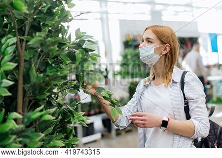 Buying Home Plants. Choosing Trees For The Garden. A Young Woman Chooses Large Deciduous Plants For