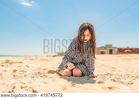 Teenager Girl Draws With A Stick On The Sand On The Beach By The Sea. Go To Dream Concept. Teenage