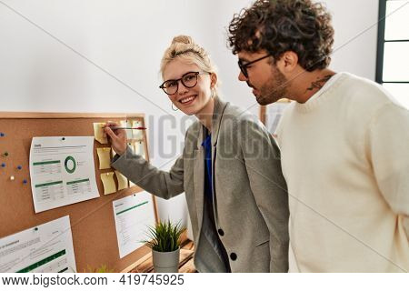 Two business workers smiling happy writing at corkboard reminder at the office.