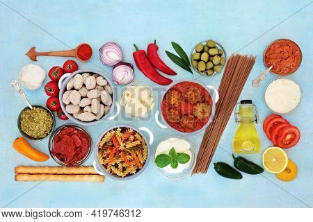 Healthy balanced Italian diet food high in antioxidants, anthocyanins, fibre, lycopene, omega 3 and protein. With meatballs, cheeses, vegetables, pasta, olive oil, sauces and herbs. On mottled blue.